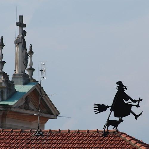 Sui tetti del paese dipinto danza la befana (o una strega?)
